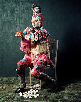 Woman In Bizarre Outfit With Knitted Russian Dolls Sitting On A Chair Holding A Dessert