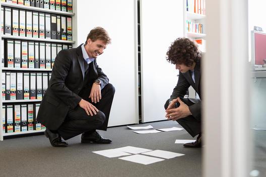 Businessmen laying paperwork on office floor