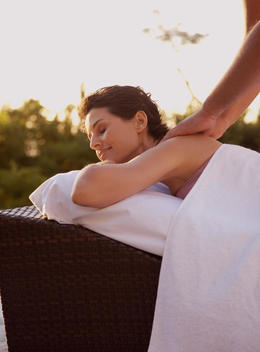Massage therapist massaging woman on shoulders outdoors