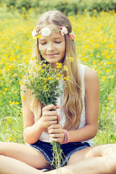 Portrait of a girl sitting on a flower meadow smelling on a bunch of flowers