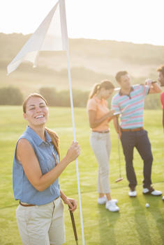 Smiling woman holding golf flag