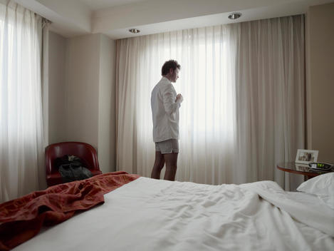Man waking up in bedroom looks out the window