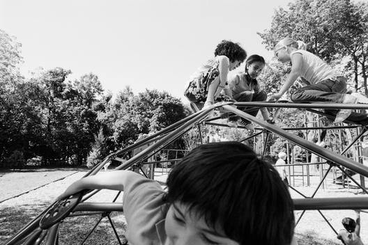 Children Hanging From Monkey Bars In Playground