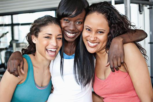 Smiling women hugging in health club