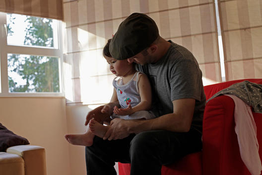 Father Wearing A Cap, Sitting On A Red Couch Holding His Toddler