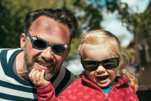 Portrait of father and daughter with exchanged sunglasses