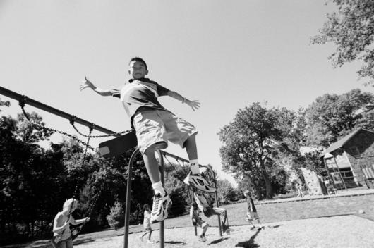 Child Jumping Off Swing In Mid-Air
