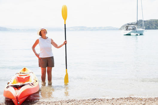 Senior woman with paddle and sea kayak