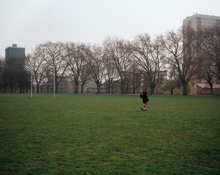 A Man Walking Across A Rugby Field With Rugby Posts In The Distance