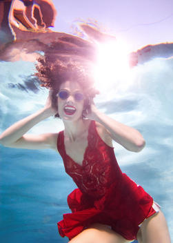 Mixed race woman in clothes swimming underwater