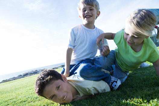 Three children wrestling on grass, smiling