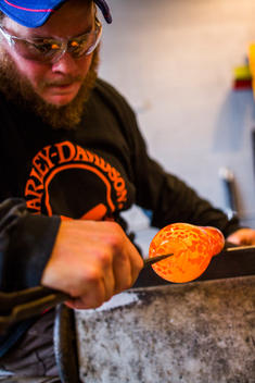 At a glass blowing studio on Whidbey Island, WA, a man makes a glass sculpture.