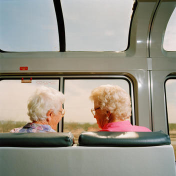 Senior Passengers On Train Chatting