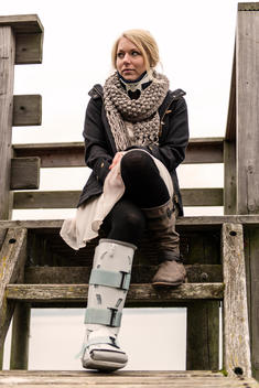 Germany, Kiel, Woman with cast and neck brace sitting on wooden steps, looking away