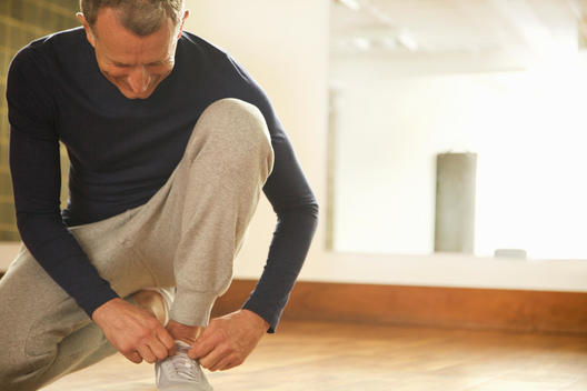 Mature Man Wearing Exercise Clothing Tying Shoelaces
