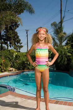 665f73fc45f Mixed race girl in bathing suit by swimming pool