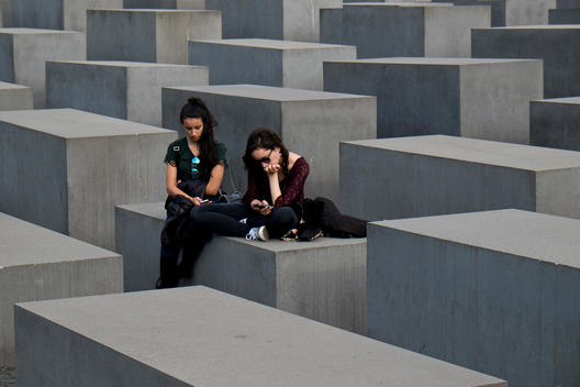 The Holocaust Memorial designed by the architect Peter Eisenman. Two girls with smart phones sitting on one of the grey concrete steal blocks.