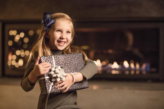 Non-specific holiday portrait of a young girl holding a gift in her arms, with a huge smile on her face. She is seated in front of a modern lit fireplace in which holiday lights are reflected on the glass.