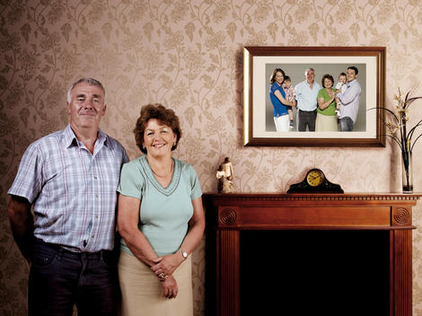 Portrait Of Senior Couple Next To Photograph Of Multiple Generations Of Their Family