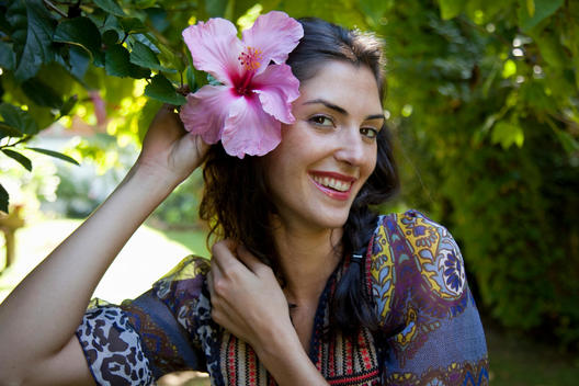 Woman Holding Hibiscus Flower To Her Ear