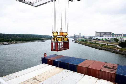 Worker unlocking containers for unloading onto the dock at the Port of Rouen on the Seine River