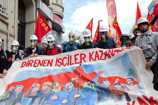 Textile industry workers wearing gas masks and carrying banners its written \'Labors Whom Resist Will Win\' during the May Day celebrations in Istanbul,