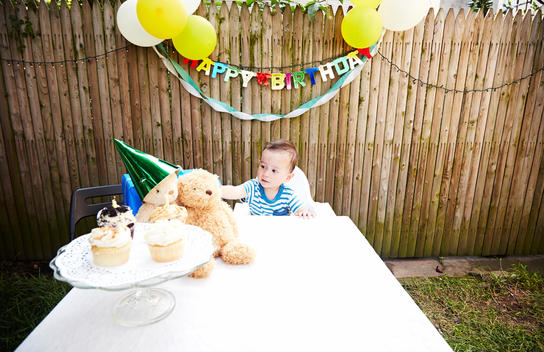 Baby boy sitting at table with soft toys wearing party hat