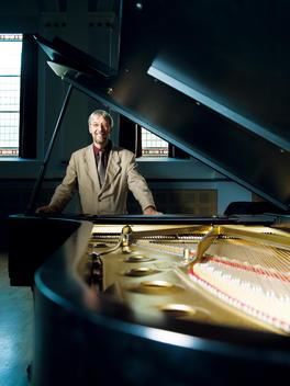 Music Teacher Standing Behind Grand Piano.