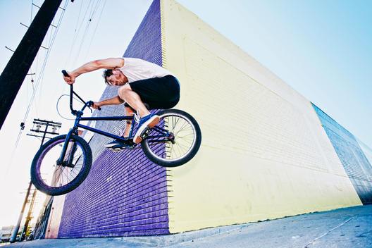 Caucasian man jumping on BMX bike on sidewalk
