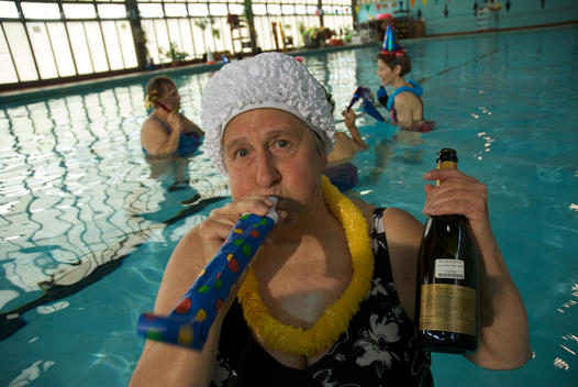 Woman In A Swimming Pool, Holding A Bottle Of Champagne And Blowing On A Party Favor