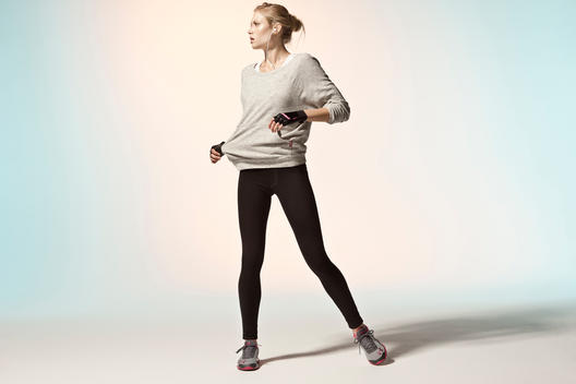 Blonde athletic girl wearing running gear in studio