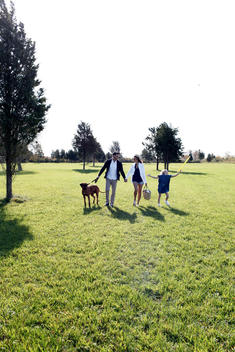 Family Walking Through Grassy Field
