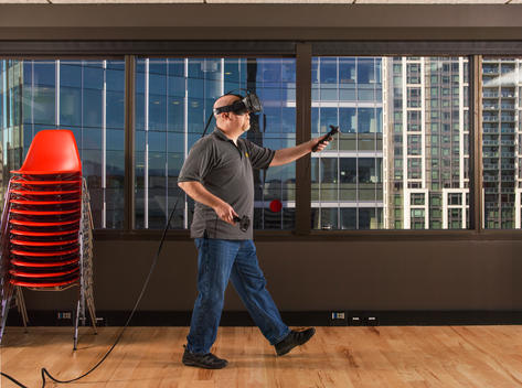 A bald male employee works on virtual reality technology in an office