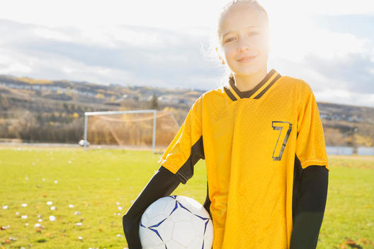 Portrait of confident soccer player with ball on field
