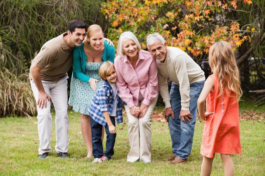Girl taking picture of extended family in garden