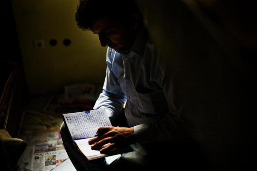 Man Writes Political Daily Diary In His Small Apartment Sharing With Other Labors In Istanbul.