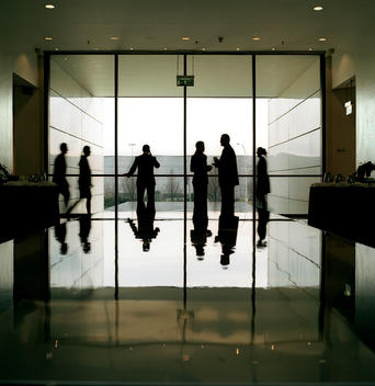 A Group Of Business Men And Women Congregate In The Lobby Of A Hotel At Gatwick Airport.