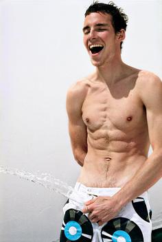 Shirtless young man sprays hose through swim trucks.