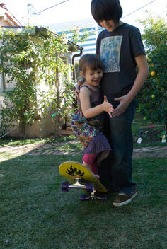 Boy Helping His Giggling Younger Sister On A Skateboard, Santa Monica