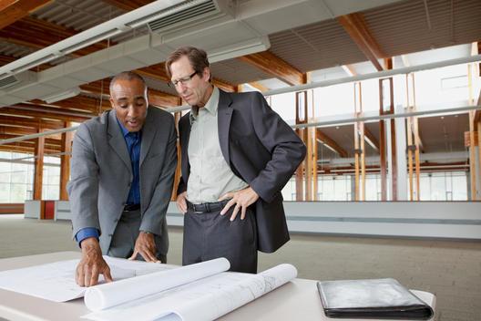 Businessmen looking at blueprints