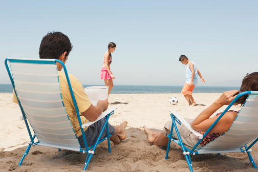 Parents watching children from lawn chairs on beach
