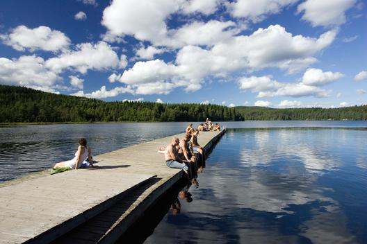 Idyllic image of young people sunbathing at Sognsvann lake, Oslo, Norway.