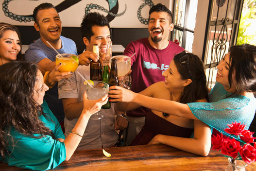 Hispanic friends toasting with drinks at bar