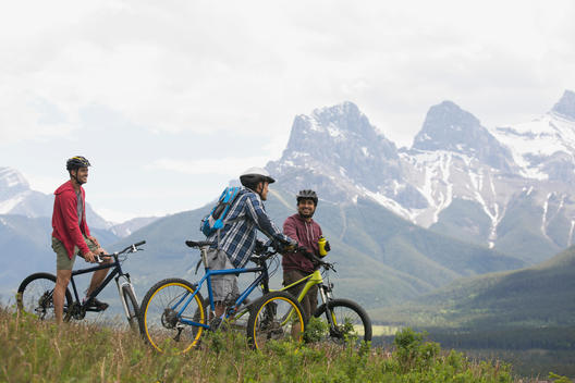 Men on mountain bikes in grass below mountains