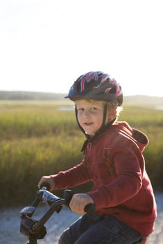 Young boy riding bicycle along marsh