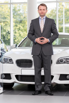 At the car dealer, Salesman standing at new car