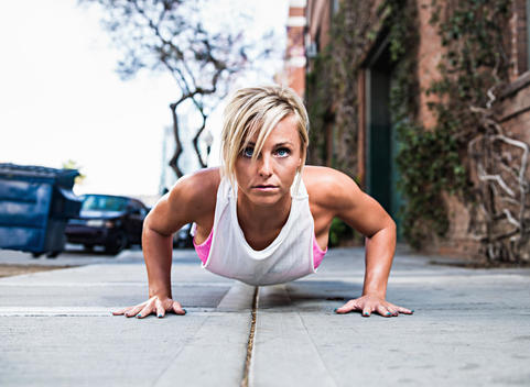 Young woman doing push-up on city street
