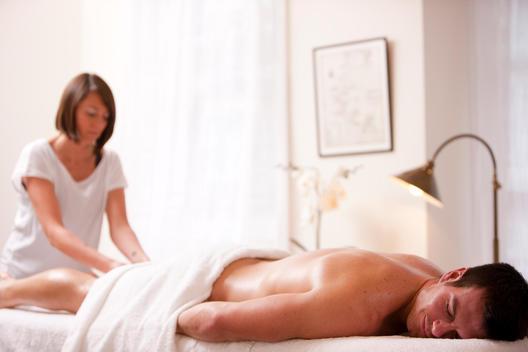 Masseuse giving a man a leg massage
