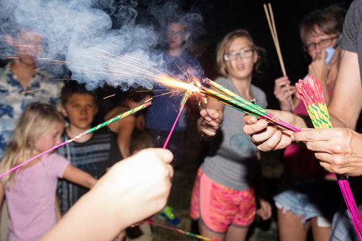 A group of kids light sparklers during the 4th of July fireworks celebration they\'re having with family on the front lawn of their suburban home. Pleasant Grove, Utah
