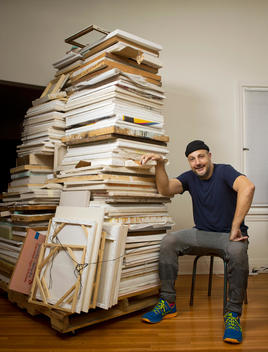 Art dealer, Stefan Simchowitz sits on a chair next to a giant piece of art